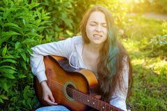 Young hipster woman sitting in grass and playing guitar on park or garden background. Teen girl learning to play song. And writing music. Hobby, lifestyle stock photos