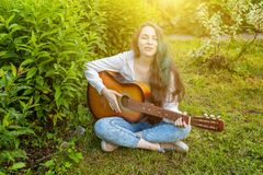 Young hipster woman sitting in grass and playing guitar on park or garden background. Teen girl learning to play song. And writing music. Hobby, lifestyle royalty free stock photography