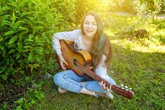 Young hipster woman sitting in grass and playing guitar on park or garden background. Teen girl learning to play song. And writing music. Hobby, lifestyle stock photo