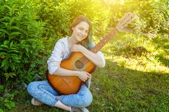 Young hipster woman sitting in grass and playing guitar on park or garden background. Teen girl learning to play song. And writing music. Hobby, lifestyle stock photography
