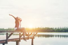 Free Young Hipster Woman Sitting On Pier Raised Hands,relaxing With N Royalty Free Stock Image - 112828886
