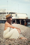 Young hipster woman sitting on a seacoast. Stock Photo