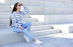 Young hipster woman in stylish jeans sitting. On stairs outdoors stock photography