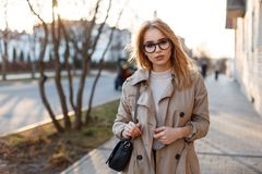 Young hipster woman in a stylish spring coat in fashionable glasses in a white T-shirt in a black leather handbag royalty free stock photography