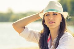 Young hipster woman at sunny beach. Beautiful caucasian girl in hat at summer midday Royalty Free Stock Photos