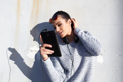 Young hipster woman with tablet and headphones outdoor Stock Image