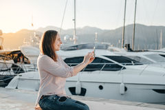 Young hipster woman taking photo  while sitting near sea port Stock Image