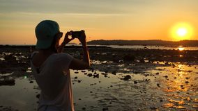 Young Hipster Woman Taking Picture with Smartphone at Amazing Sunset. HD Slow Motion. Thailand. stock video footage