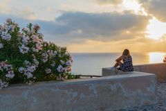 Young hipster woman traveler looking at sunset and beautiful seascape in summer vacation with a lookout point stock photography