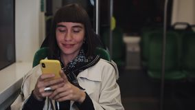 Young hipster woman using smartphone sitting in public transport, steadicam shot. Young woman receives good news on. Smartphone. Slow motion. City lights stock video footage