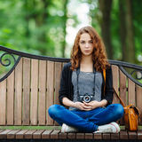 Young hipster woman with a vintage film camera on the bench Royalty Free Stock Photo