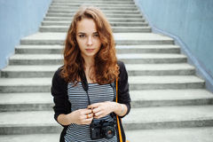 Young hipster woman with a vintage film camera on stairs Stock Images