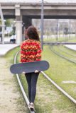 Young hipster woman walks by old rail in the street. Royalty Free Stock Images