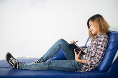 Young hipster woman  writing on notepad lying at home . Stock Photo