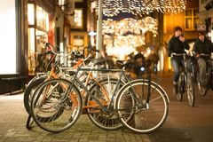 young hipsters cyclists ride past bicycle parking in a European city late at night. stock image