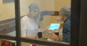 Young hipsters drinking beer and using pad in cafe. Young hipster style man and woman spending time in cafe. They having beer and discussing something using stock footage