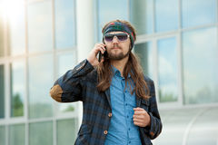 Young hipsters with the phone. Young hipster fashion guy with beard talking on the phone and walking through the city Royalty Free Stock Photo