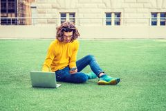 Young Hispanic American College Student Studying in New York. Hispanic American College Student studying in New York, with brown curly hair, wearing glasses Royalty Free Stock Image