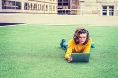 Young Hispanic American College Student Studying in New York. With curly hair, wearing glasses, long sleeve T shirt, jeans, sneakers, lying on green lawn on Royalty Free Stock Photography