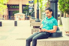 Young Hispanic American College Student texting outside in New Y. Young Hispanic American College Student, wearing green patterned Polo shirt, black pants Royalty Free Stock Image