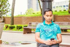 Young Hispanic American College Student texting outside in New Y. Young Hispanic American Man wearing green patterned Polo shirt, sitting against light pole on Royalty Free Stock Photo