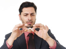 Young hispanic attractive man breaking cigarette in quit smoking resolution Royalty Free Stock Image