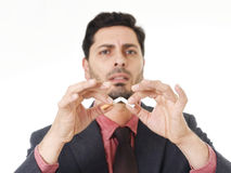 Young hispanic attractive man breaking cigarette in quit smoking resolution Royalty Free Stock Photo