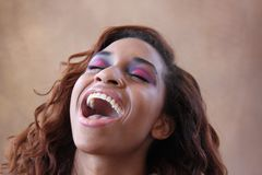 Young hispanic black woman lifts her head up laughing. Young hispanic black woman in her 20s with unusual eye makeup and a light lip color lifts her head upward Royalty Free Stock Photos