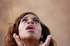 Young hispanic black woman looking up. Young hispanic black woman in her 20s with unusual eye makeup and a light lip looking up, with her hands beneath her face Stock Image