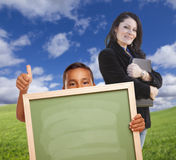 Young Hispanic Boy with Blank Chalk Board, Teacher Behind on Grass Stock Image