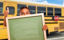 Young Hispanic Boy with Blank Chalkboard Near School Bus. Cute Young Hispanic Boy with Blank Chalkboard Near School Bus Giving a Thumbs Up stock photo