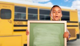 Young Hispanic Boy with Blank Chalkboard Near School Bus stock photo