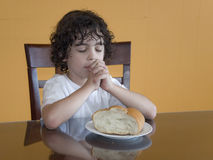 Young Hispanic Boy Praying for the Daily Food. Royalty Free Stock Photos