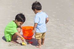 Young Hispanic Boys Children Brothers Playing Beach. Two happy young hispanic boys brothers playing together on a sunny tropical beach with buckets and spades Stock Photos