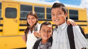Young Hispanic Boys and Girl Walking Near School Bus stock images