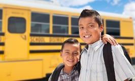 Young Hispanic Boys Walking Near School Bus. Two Young Hispanic Boys Near School Bus Wearing Backpacks stock photos