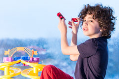 Young Hispanic child playing indoors because of a rainy day. Bad weather consequence. Latin boy playing with small toys inside his home because of bad weather royalty free stock photos