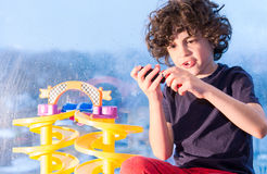 Young Hispanic child playing indoors because of a rainy day. Bad weather consequence. Latin boy playing with small toys inside his home because of bad weather royalty free stock photo