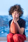 Young Hispanic child praying so the weather improves and he can go to play outdoors. Latin young boy praying to be able to play outside his home. Inside his home Royalty Free Stock Images