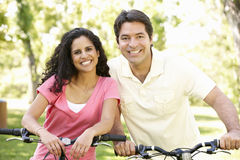 Young Hispanic Couple Cycling In Park Royalty Free Stock Images