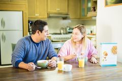 Couple together eating breakfast at home. Young hispanic couple enjoying breakfast together in their kitchen and looking at each other Royalty Free Stock Photos