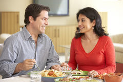 Young Hispanic Couple Enjoying Meal At Home Stock Image