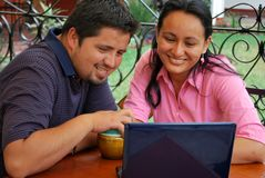 Young Hispanic couple with laptop. A cute, young Hispanic couple together at a cafe Royalty Free Stock Photos