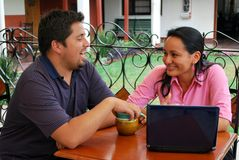 Young Hispanic couple with laptop. A cute, young HIspanic couple together at a cafe Royalty Free Stock Images