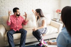 Couple quarreling in front of therapist. Young hispanic couple quarreling in front of their therapist in the office Royalty Free Stock Images