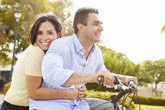 Young Hispanic Couple Riding Bikes In Park Stock Photo