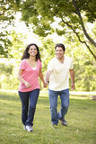 Young Hispanic Couple Running In Park Royalty Free Stock Photos