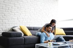 Girl Massaging Boyfriend On Sofa At Home Royalty Free Stock Images