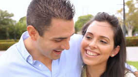 Young Hispanic Couple Walking Through Park Together. Camera tracks happy couple as they walk through park and talk. Shot on Canon 5D MkII at frame rate of 25fps stock video footage