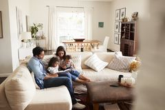 Young Hispanic family sitting on sofa reading a book together in the living room, seen from doorway royalty free stock photo